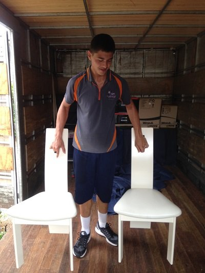 Platinum Furniture Removalist standing with two chairs.