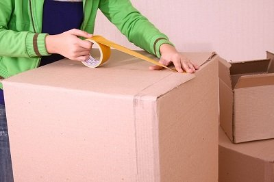 A lady using masking tape on a box for moving house.