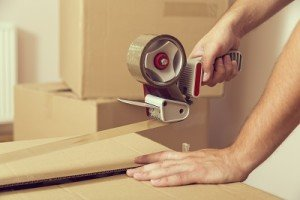 A hand taping up a cardboard box for removals.